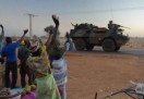 Malian people wave to French soldiers